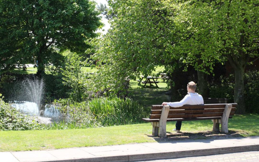 office-worker-sat-on-bench-by-pond